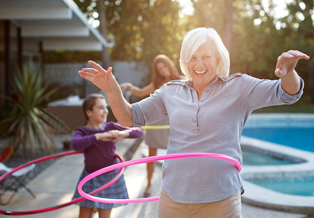 Older woman hula hooping in backyard, 10 Things You Need to Know About the Health Care Law