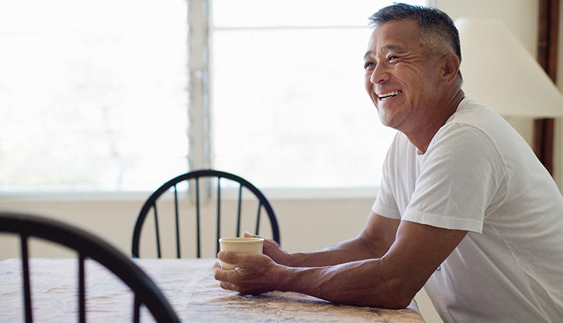 Un hombre sentado a la mesa con una taza en su mano