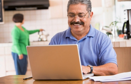 Hispanic man using laptop, Health Insurance Terms Quiz
