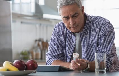 Hombre mirando un frasco de medicinas - Costos Medicare