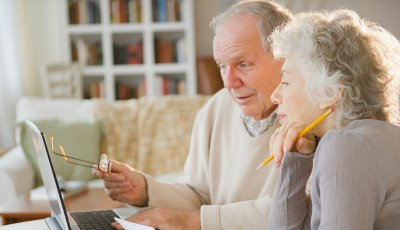 Senior-couple-going-over-bills-with-laptop