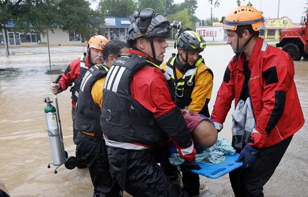Rescatistas llevan a una víctima del huracán Harvey en una camilla