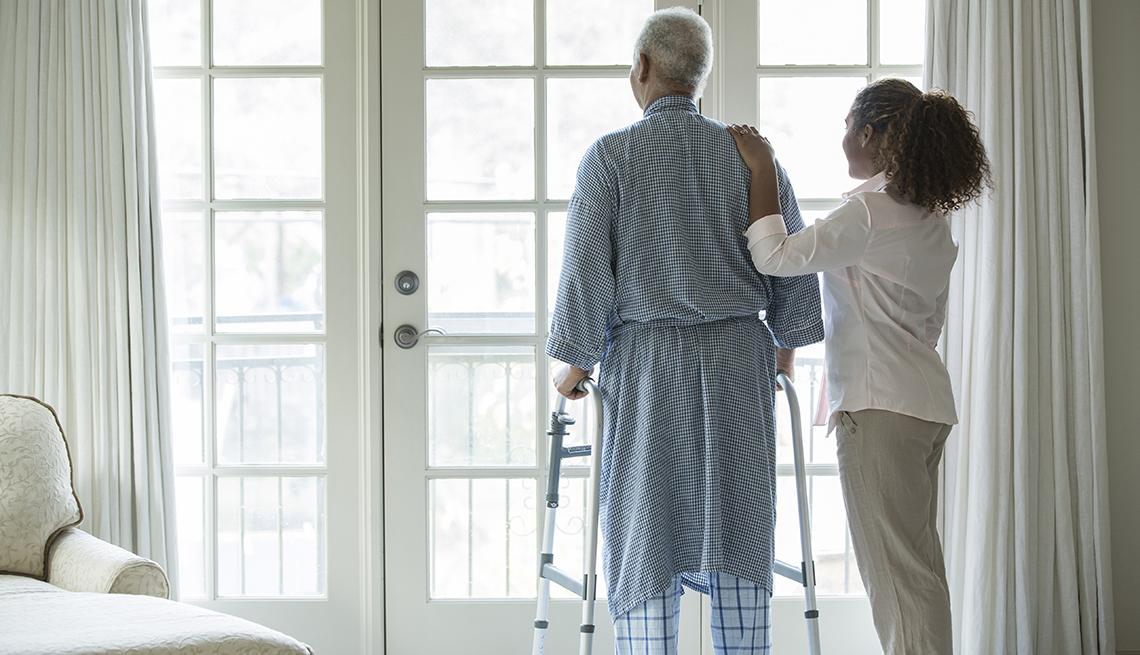 Mujer ayudando a un hombre con un andador