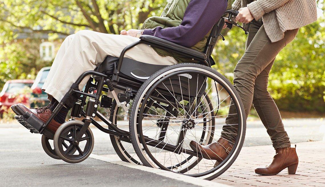 Persona en silla de ruedas, mientras otra persona lo lleva
