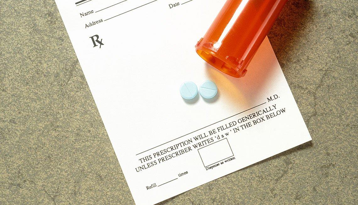 Receta médica y frasco con pastillas sobre ella