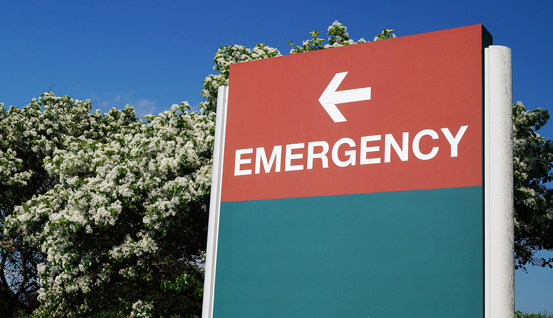 An outdoor green and red sign pointing in the direction of the hospital emergency department.