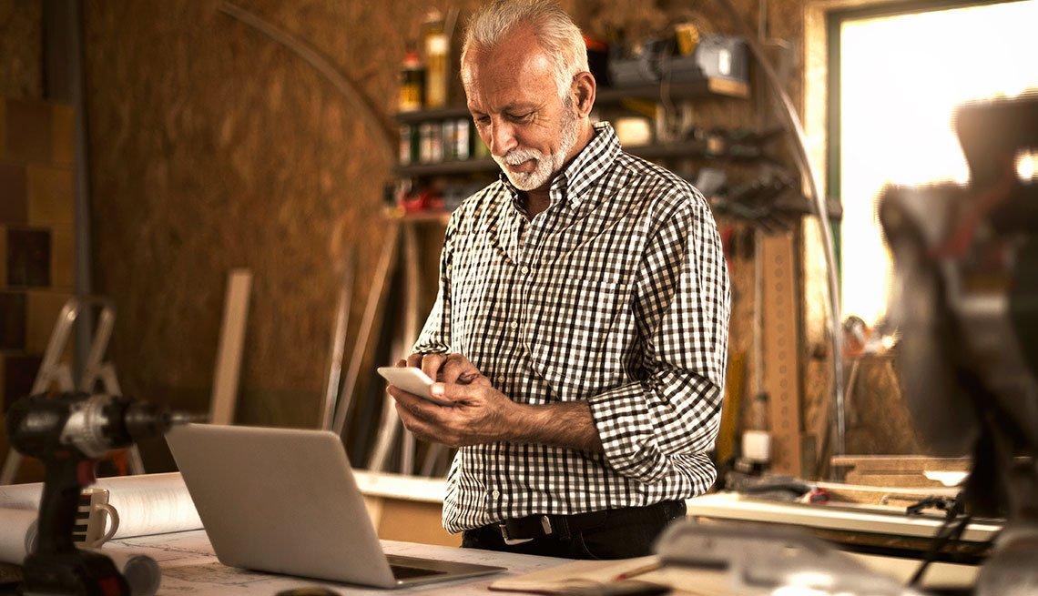 Hombre en su celular frente a su computador