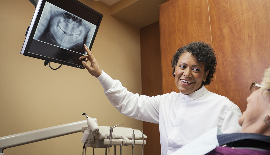 Dentist pointing to the dental x-ray on a screen while patient in the chair watches.