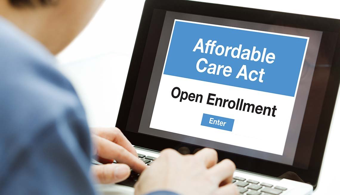 A man using a laptop computer and the internet web service, he is in the process of signing up and joining the Affordable Care Act Obamacare in the United States in the open enrollment for his healthcare insurance plan.