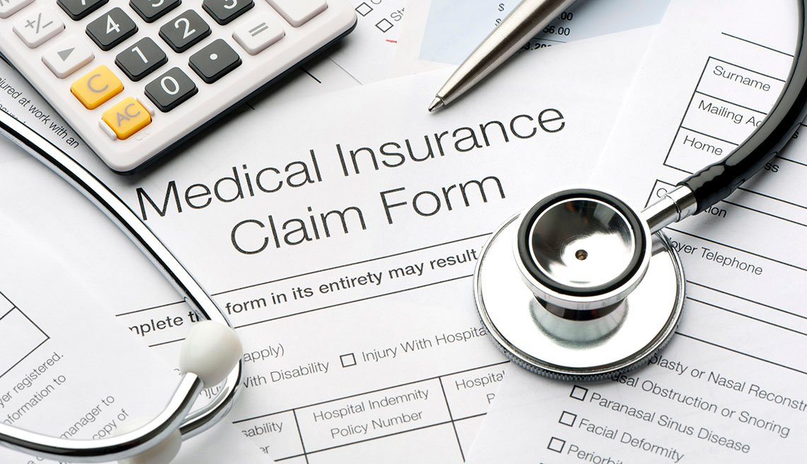 Medical insurance forms next to a calculator, stethoscope and pen