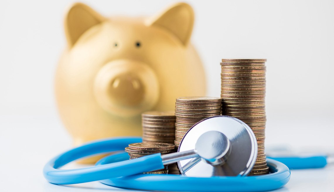 A coin stack with stethoscope and gold piggy bank on white background.