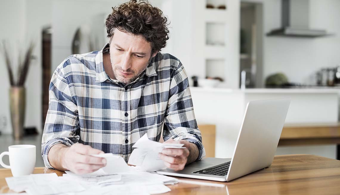A man is reading bills while making online payment at home