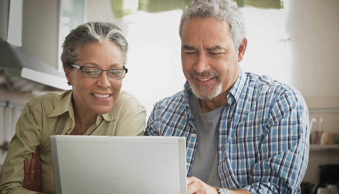 Una pareja de adultos mayores usa una computadora