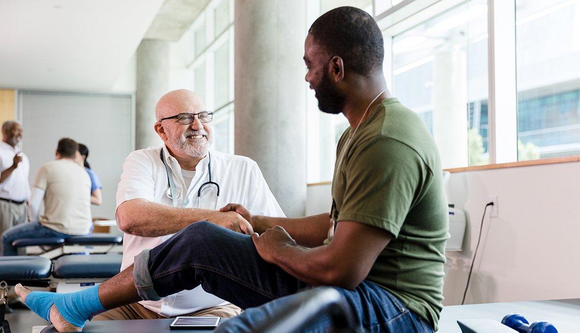 Un hombre sentado en una cama siendo atendido por un médico