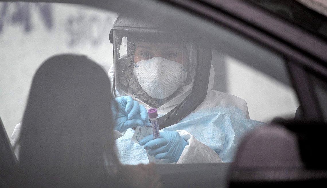 Una enfermera con uniforme protector examina a una persona en su auto