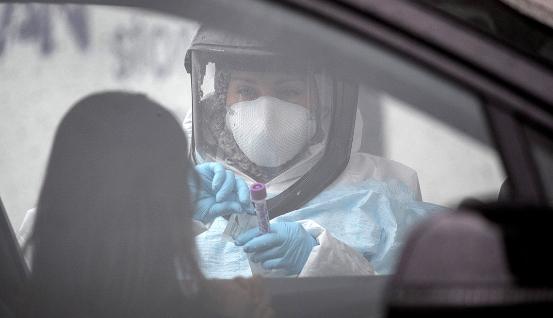 A nurse dressed in personal protective equipment prepares to give a coronavirus swab test at a drive thru testing station at Cummings Park in Stamford Connecticut.