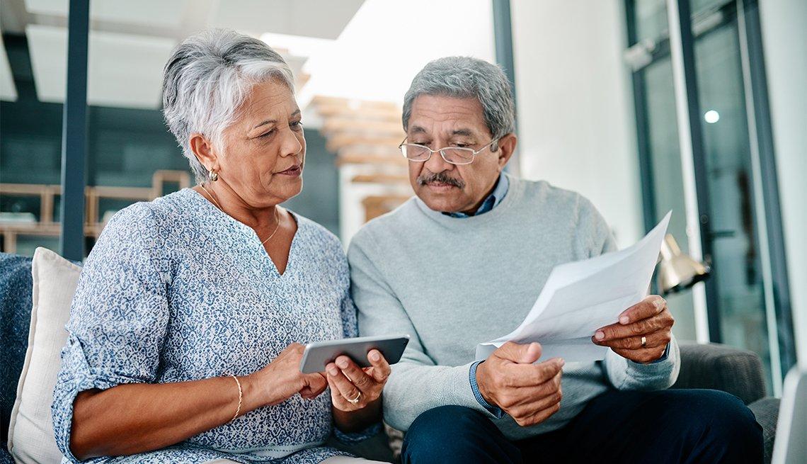Pareja de adultos mayores miran unas facturas médicas