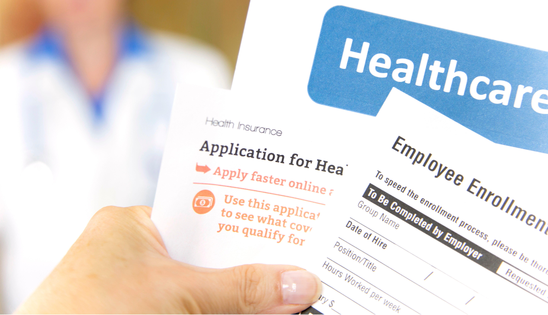Una mano sostiene varios formularios de solicitud de planes médicos
