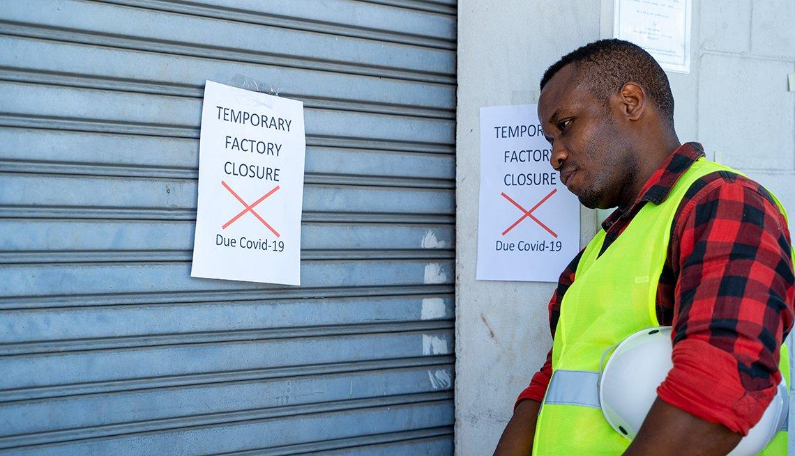 Un obrero mira una puerta cerrada con un letrero que dice 'cerrado temporeramente por COVID-19'