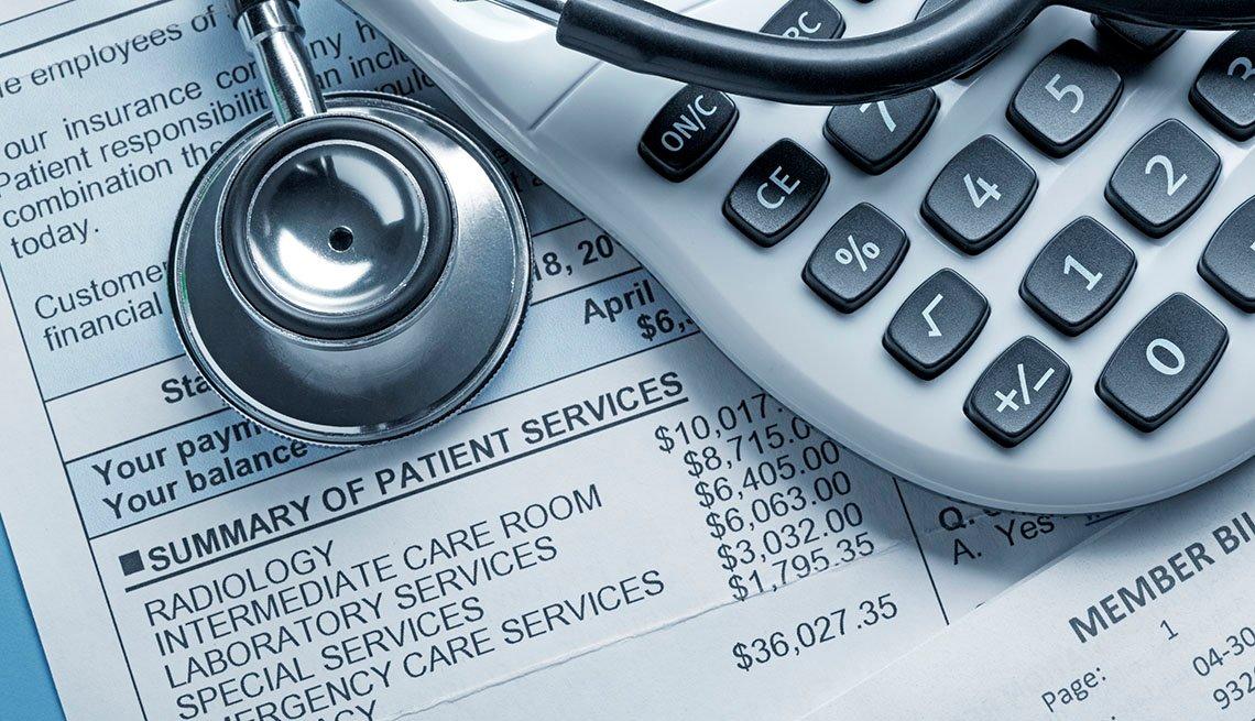 Un estetoscopio y una calculadora sobre una factura médica