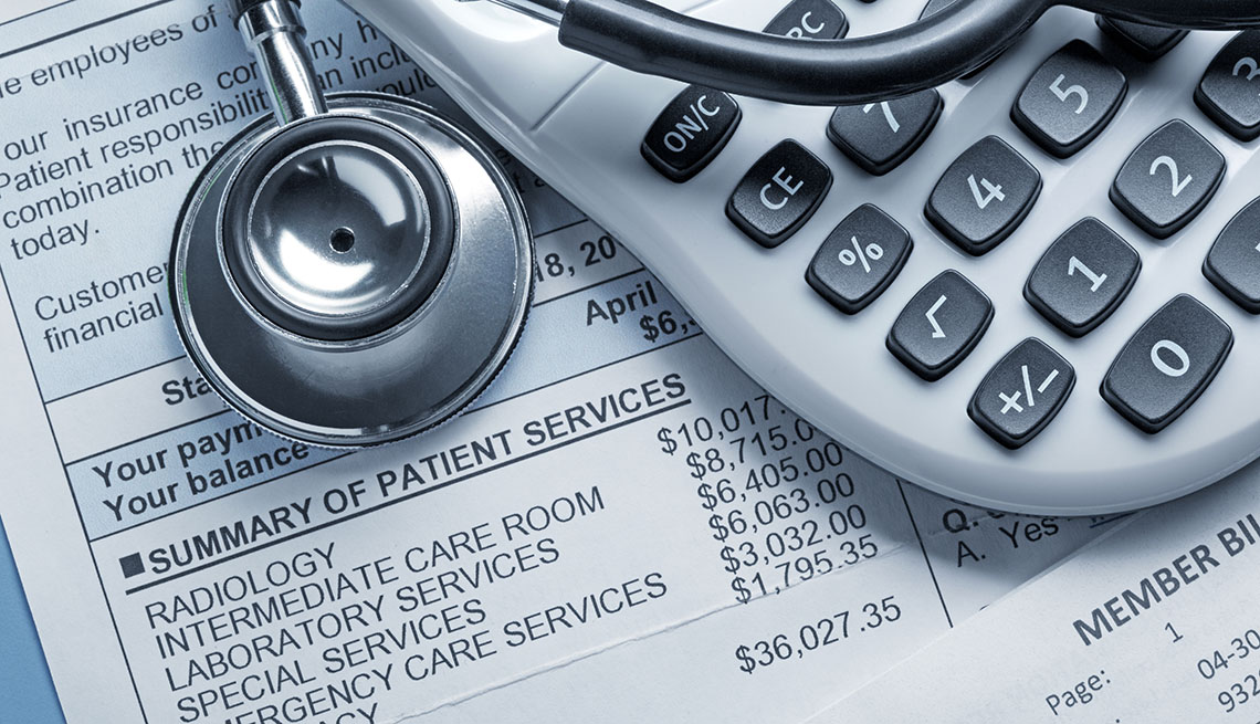 a stethoscope and a calculator rest on top of a medical bill.