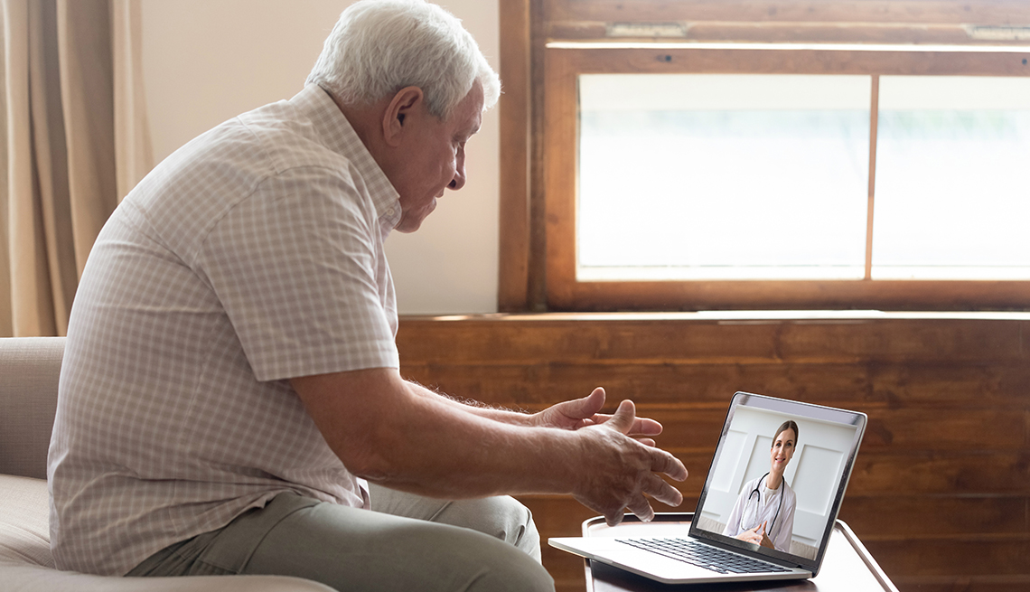 A man talks with his doctor on a laptop