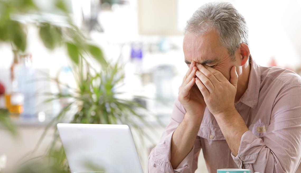 Un hombre con la cara entre las manos sentado frente a su computadora