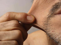 men get cosmetic surgery - man pinches cheek