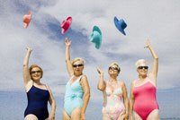 Group of senior women in bathing suits tossing hats in air