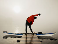 A kayaker stretches before entering his boat