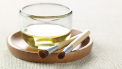olive oil in a jar and two nail brushes
