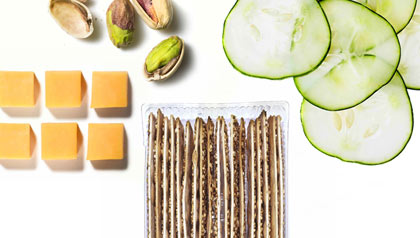 Cheese, pistachios, cucumbers and whole grain crackers. Healthy snacks.