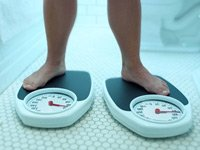 Foto de los pies en dos escalas. Un extra de diez libras puede ayudar a la salud después de 50 años de edad.