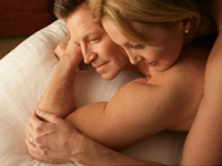Couple in bed. Among other things, having sex frequently can lower your risk of developing prostate cancer.