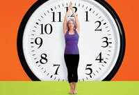 Woman stands in front of a giant clock - Dr. Oz 24 hours to a longer life