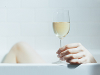 Woman relaxing with glass of wine in tub. Will drinking alcohol increase your risk of developing breast cancer?