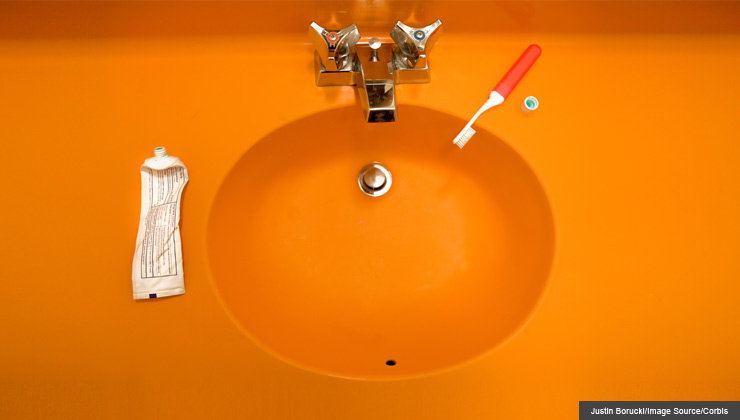 View of toothpaste, toothbrush and bathroom sink. Good oral hygiene is necessary for healthy teeth and gums.