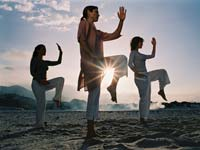 Friends Practicing Tai-Chi On Beach At Dawn