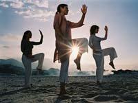 Friends Practicing Tai-Chi On Beach At Dawn