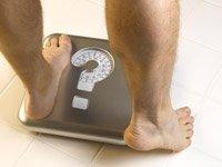 Encuesta sobre la grasa en el estómago - Hombre sobre una escala que tiene un signo de interrogación sobre ella.