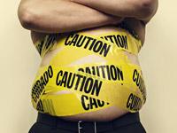 Cómo eliminar la grasa abdominal - Hombre sin camisa con su cintura envuelta en cinta amarilla de precaución.