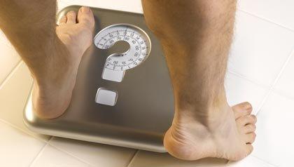 200556971-001,x-defaultEncuesta sobre la grasa en el estómago - Hombre sobre una escala que tiene un signo de interrogación sobre ella.