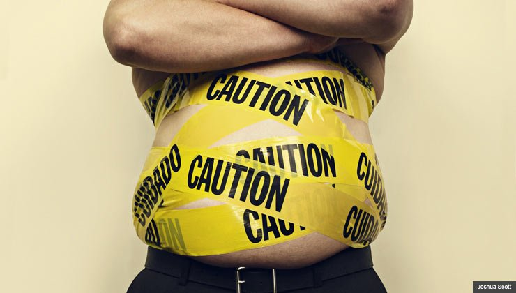 Shirtless man with his waist is wrapped in yellow caution tape