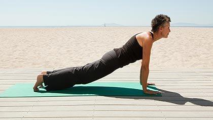 Mujer madura haciendo yoga en la playa