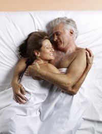 Pareja abrazándose en la cama - Qué puede esperar en sus años 50s, 60s y 70s y más allá