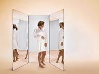Mujer mirándose en un espejo - Qué puede esperar en sus años 50s, 60s y 70s y más allá