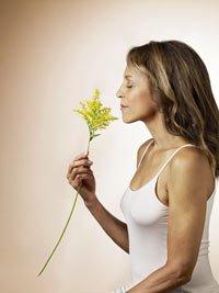 Mujer en actitud meditando con una flor en la mano - Qué puede esperar en sus años 50s, 60s y 70s y más allá