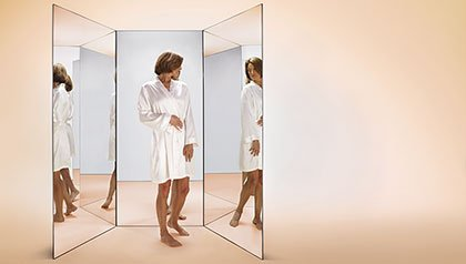 woman; mirror; flaws; health; 60s; wrinkles; age spots