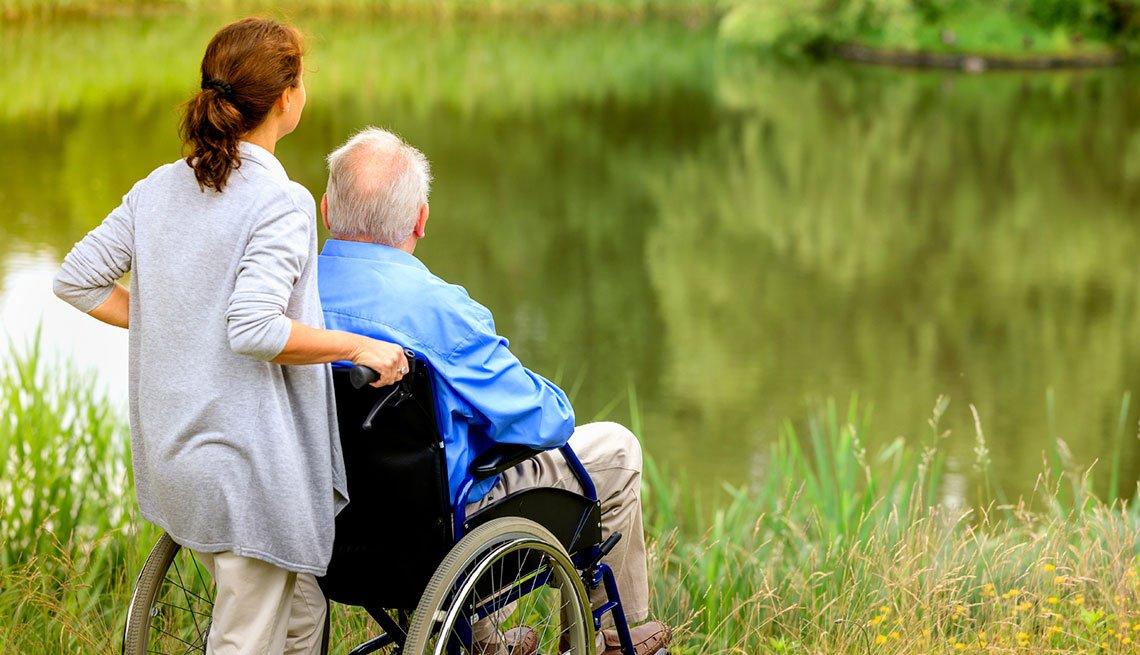 Mujer y un hombre en sillón de ruedas disfrutan de la naturaleza.