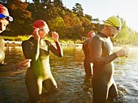 Group of triathletes in water preparing for swim -  Mini triathalons are the new fitness trend